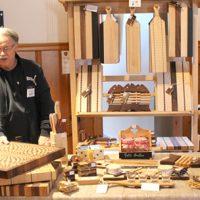 M. André Hamel, gagnant du concours Le plus bel étal 2019, devant son kiosque, expliquait avec passion le type de bois choisi pour fabriquer une place à découper ou une planche à fromage. – Photo : Yves Briand
