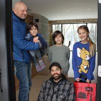 Zofia, Milann, Mareck avec papa et grand-papa, heureux de participer à la guignolée, une belle leçon de vie! – Photo : Yves Briand